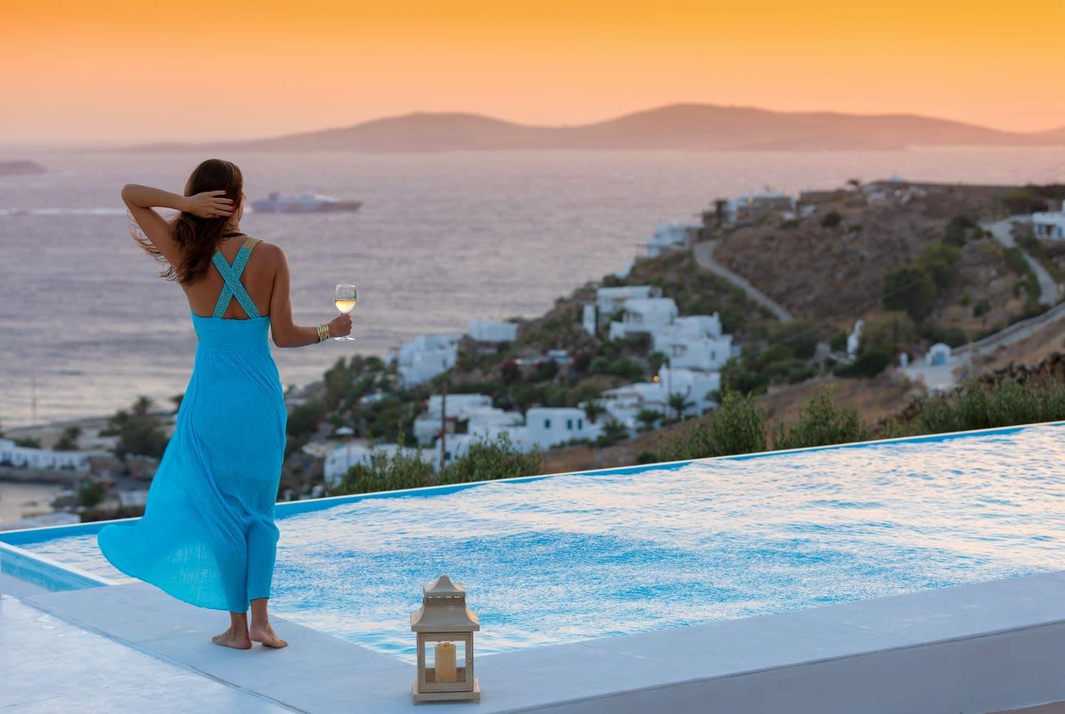 Attraktive Frau in blaume Kleid steht am Pool mit einem Weinglas und schaut auf den Sonnenuntergang